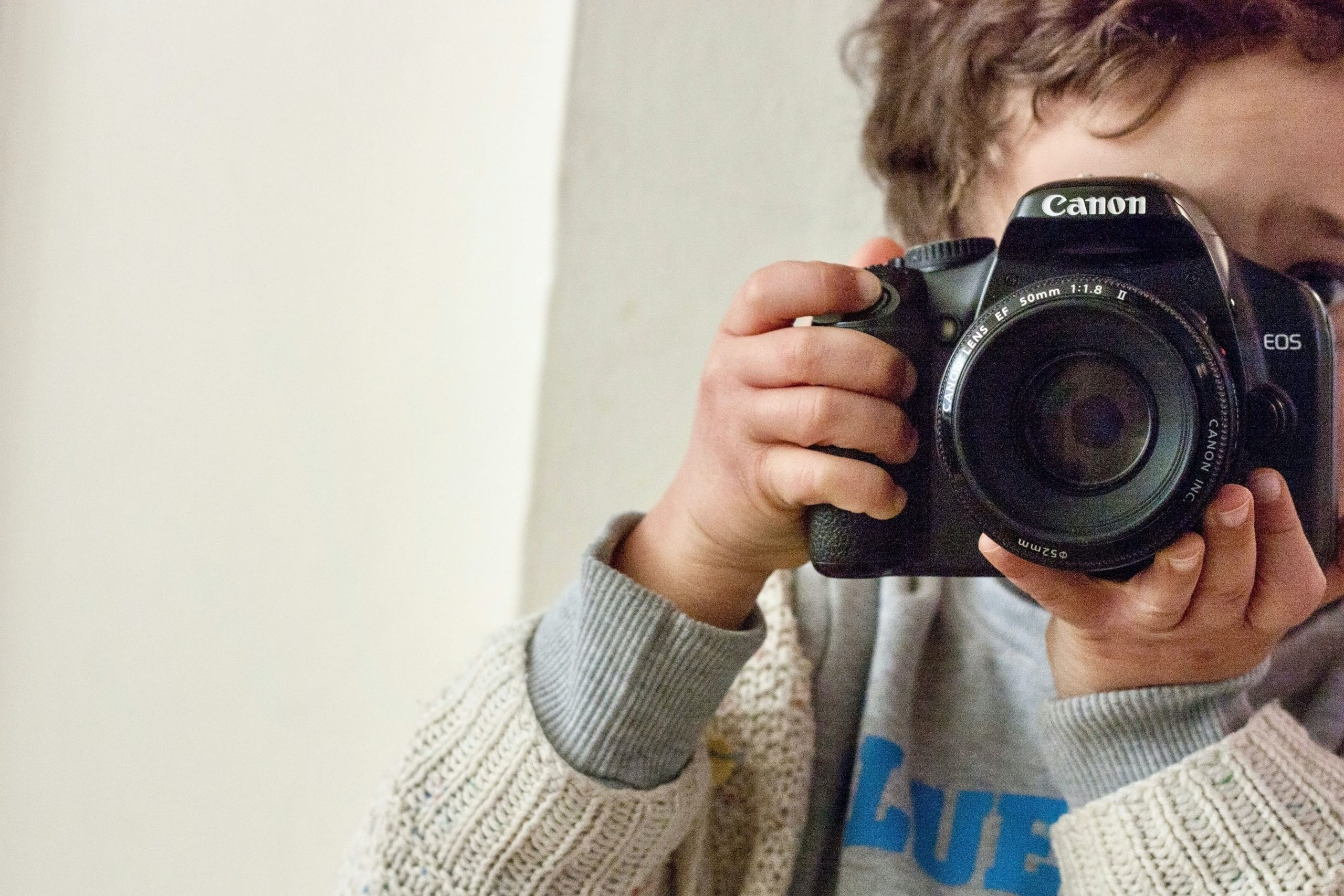child taking a picture with a DSLR camera