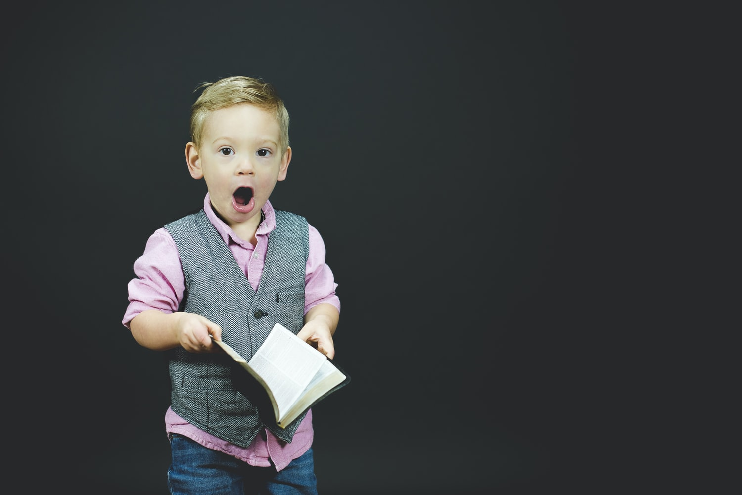 little boy holding a book looking amused