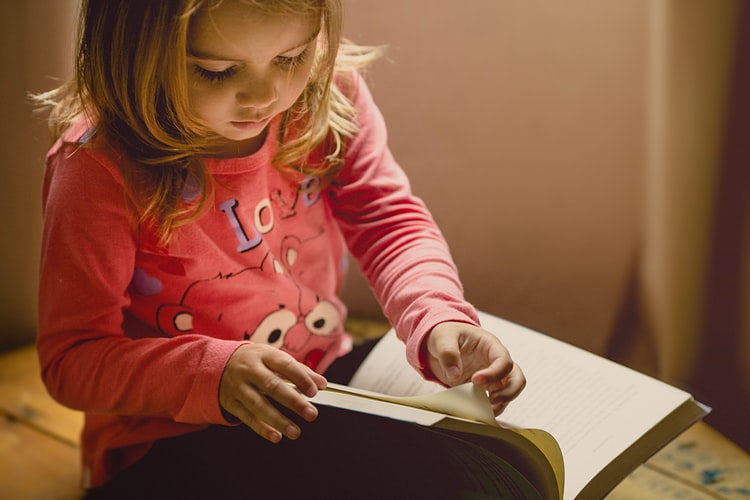 little girl in a pink shirt reading a book