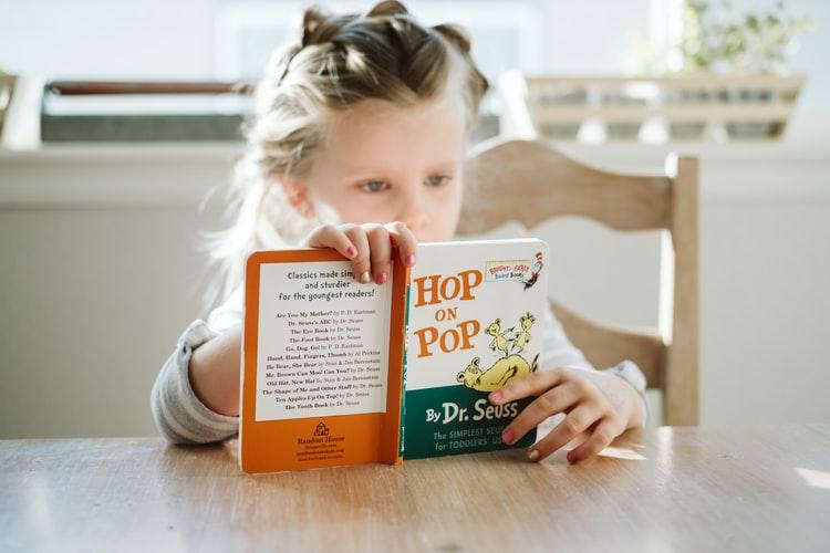 little girl reading hop on pop by dr seuss