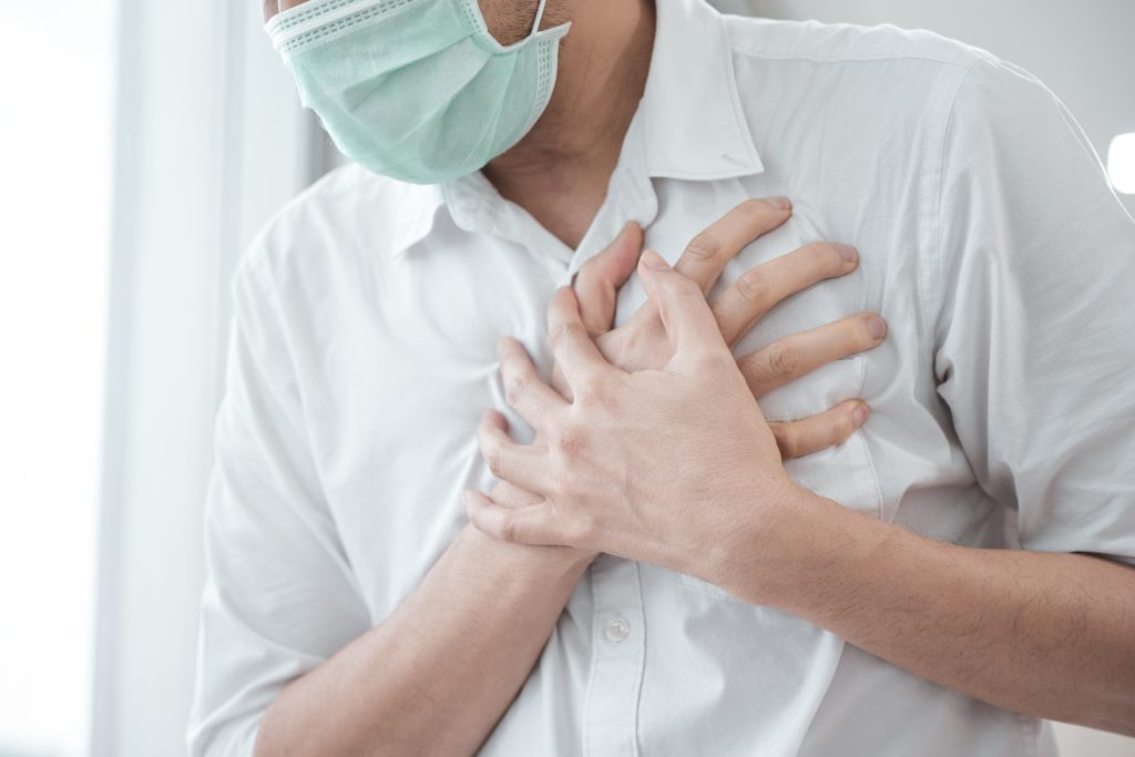 man wearing a mask having a heart attack