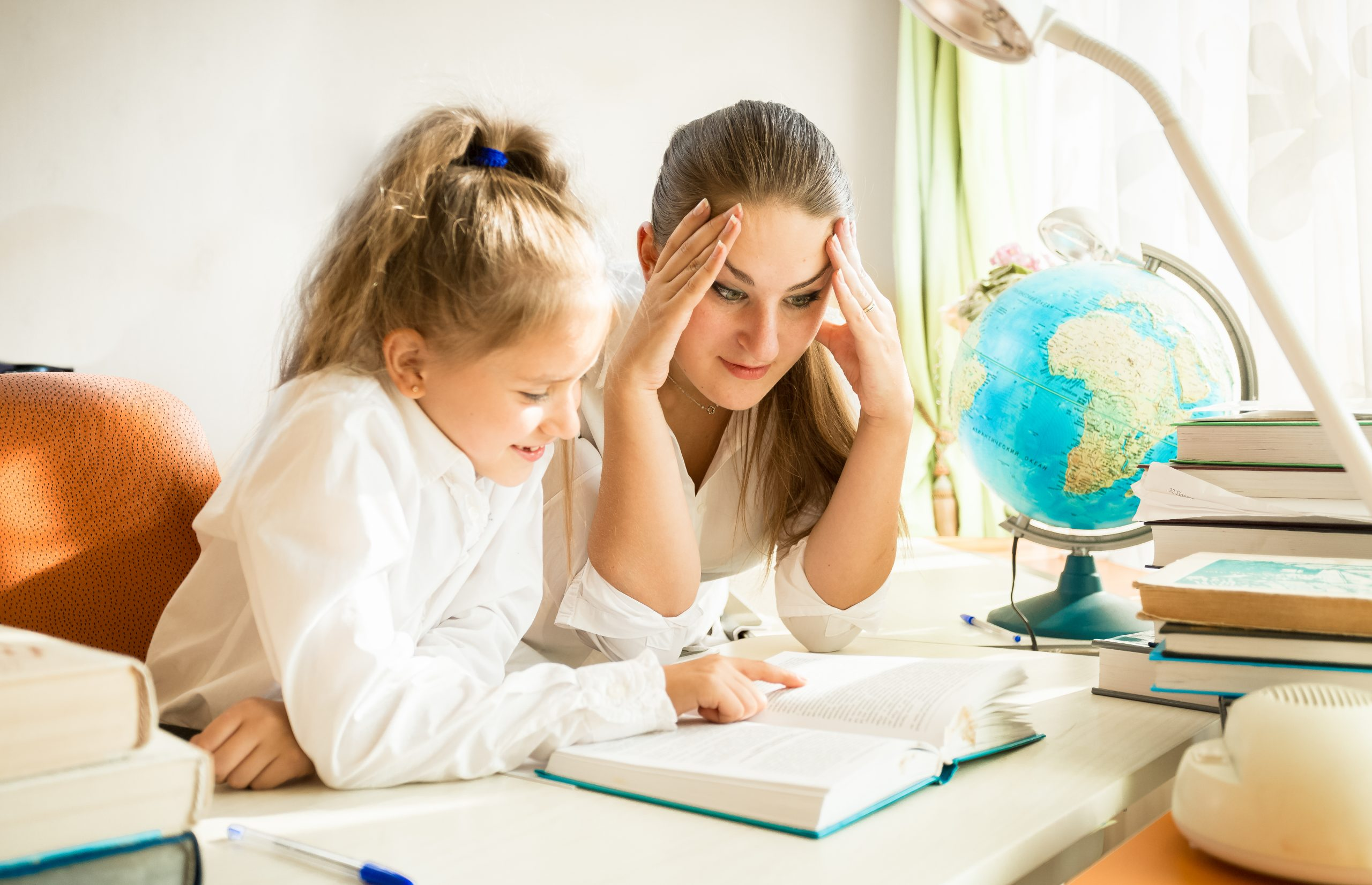 little girl reading a book with her mother