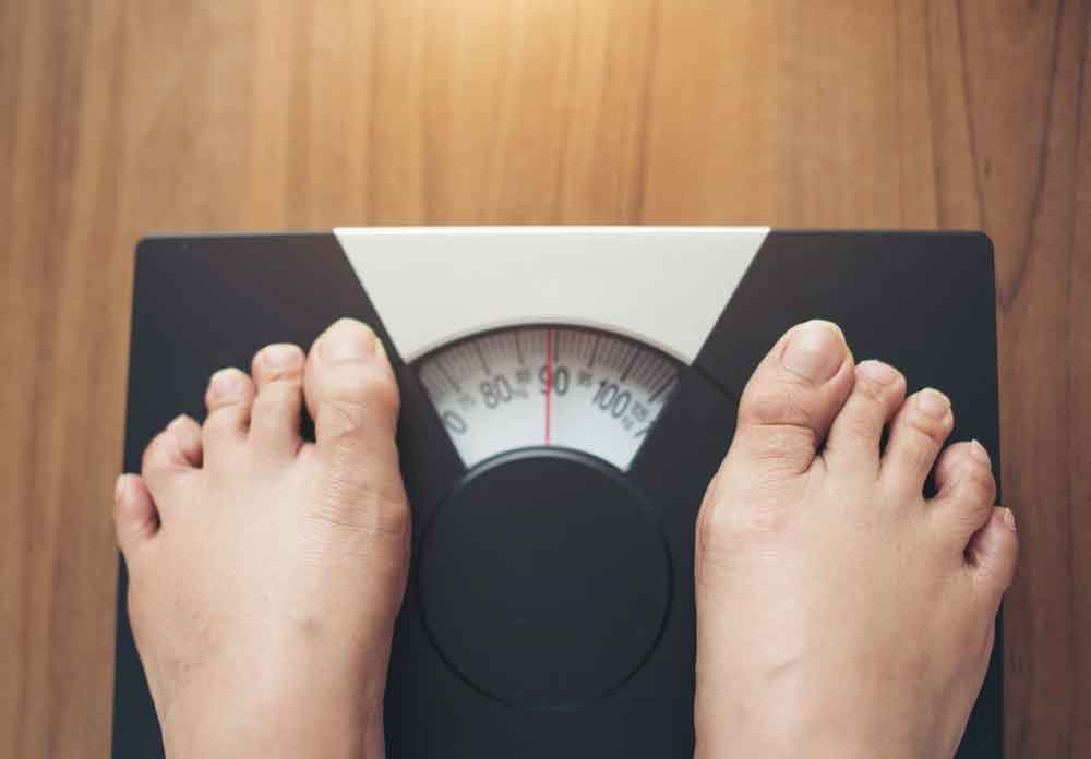 person checking their weight on a weighing scale